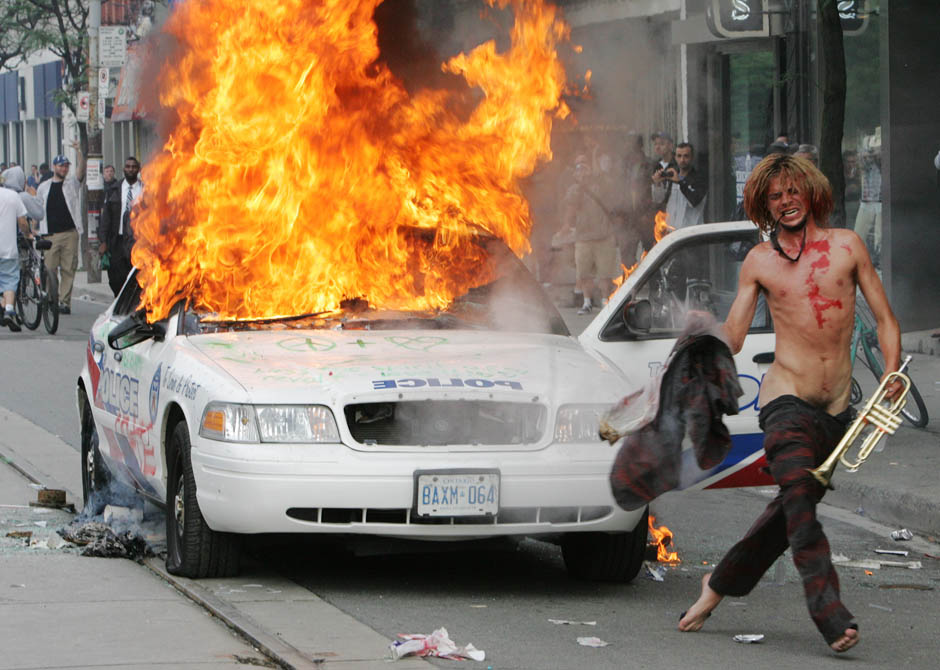 A man with a trumpet and a burning police car